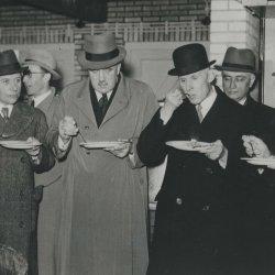 Groep mannen die haring eten.