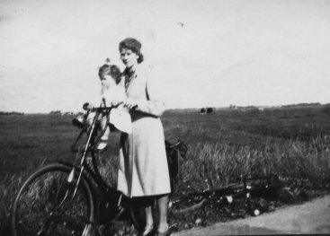 Vrouw met een kind op haar fiets.