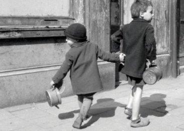 Twee kinderen die elkaars hand vasthouden en op weg zijn naar de boeren.