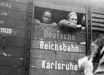 Two men  in a train wagon looking out of a small gap. On the wagon it says: 'Deutsche Reichsbahn'.