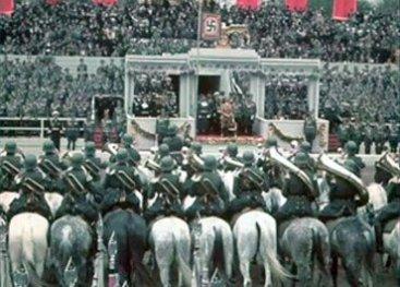 Massabijeenkomst van nazi's met Hitler. Het hakenkruis is overal te zien. Het hakenkruis wordt een teken (symbool) voor onvrijheid, geweld en vernietiging van miljoenen mensenlevens.