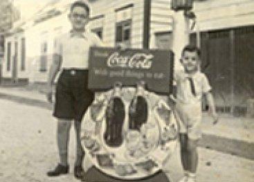 Jongens met een cola-reclamebord.
