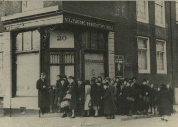 Mensen staan in de rij voor een slagerij in Amsterdam.